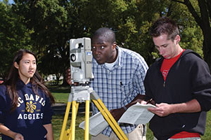 three students using surveying equipment on the Mrak Mall