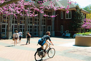 A student riding a bicycle in front of Dutton Hall