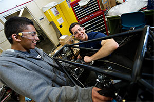 Two male students working on a racecar in the engineering department