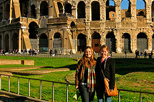 Two female students pose in front of the Roman coliseum