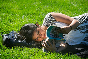 A female student laying on the grass of the quad, reading a book