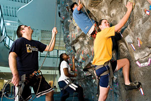 A group of students enjoys the indoor climbing wall at the ARC